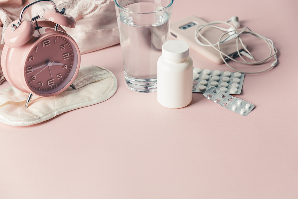 Alarm clock, eye mask, pills and glass of water on pink background